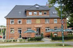 Verwaltungsgebäude der Bahngesellschaft am Bahnhof  Wismar; an der Fassade des Gebäudes, das jetzt  unter anderem als Restaurant genutzt wird, befindet sich ein  Flügelrad als Symbol der Eisenbahn als Relief an der Hausfassade.