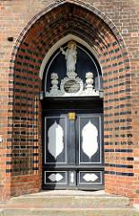 Mit reichem Schnitzwerk versehene Eingangstür mit Portal an der unter Denkmalschutz stehenden Sankt Nikolaikirche in der Hansestadt Wismar.