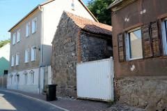 Architektur in der Stadt Oderberg, Wohnhaus mit Feldsteinfundament und Holz Luken, daneben ein Speichergebäude mit Feldsteinmauer.