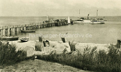 Altes Foto von der Seebrücke in Kühlungsborn, die 1929 errichtet wurde. An dem Landungssteg legten Dampfschiffe/Ausflugsschiffe an. Im Vordergrund der Strand mit Sandburgen und Strandkörben, einige  Ruderboote sind an Land gezogen.
