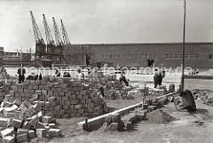 Der Platz vor dem Verteilungsschuppen 58 am Togokai des Südwesthafens wird von Straßenarbeitern gepflastert. Die Laderampen sind für die Be- und Entladung von LKW vorgesehen. Eine Schubkarre aus Holz liegt auf der Seite.