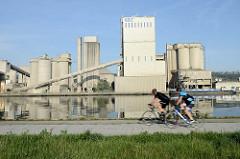 Industrieanlage am Ufer des Albert Kanals in Belgien; im Vordergrund fahren zwei Rennradfahrer auf der Kanalstraße Richtung Lüttich.
