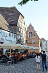 Historische Wohnhäuser und Speicher in der Altstadt von Wismar, am Lohberg - Restaurants mit Außengastronomie unter Sonnenschirmen.