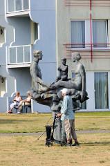 Kunst im öffentlichen Raum - Skulptur Familie mit Kind auf der Freizeitwiese einer Hotelanlage an der Strandpromenade von Kühlungsborn.