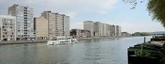 Hochhäuser am Ufer der Maas in Lüttich / Liège. Ein Fluss-Shuttle / La navette fluviale fährt die Maas flussabwärts. Rechts liegen Binnenschffe am Quai Godefroid Kurth.