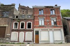 Leerstehende  Wohnhäuser / Geschäfte, Cafeteria - Vise/Cheratte, Belgien. Im Hintergrund der Turm von Schacht Nr. 1 der Kohlengrube Hasard de Cheratte.