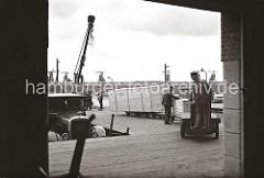 Ein Henschel Lastwagen mit dem Markenzeichen, einem Stern und den Buchstaben HuS / Henschel und Sohn am Kühler, steht an der Laderampe des Hafenschuppens 58. Der Transportarbeiter fährt die Elektrokarre mit den gerade abgeladenen Holzkisten.