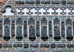 Terrakotta-Relieffiguren an der Fassade der Nikolaikirche in der Hansestadt Wismar.