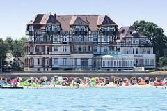 Blick auf den Ostseestrand mit Strandkörben und badenden Touristen in Kühlungsborn; dahinter das  Hotelgebäude Schloss am Meer - Strandhotel in neugotischer Architektur.