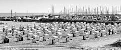 Strandkörbe stehen dicht an dicht am Ostseestrand im Seebad Kühlungsborn, dahinter die Marina mit Segelschiffen und Motorbooten.