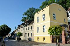Neubau eines Wohnhauses mit TonnenDach, daneben ein denkmalgeschütztes Gebäude in der Angermünder Straße von Oderberg.