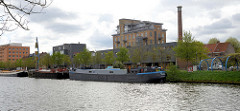 Binnenschiffe liegen am Kolenkaai des Gent- Oostende Kanals  in Brügge; am Kanalufer stehen moderne und historische Gebäude.
