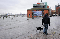 Bei Hochwasser ist der Altonaer Fischmarkt in Hamburg regelmässig überspült - Spaziergänger mit Hund geniessen das Ereignis.