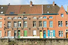 Ältere Wohnhäuser am Kanal in der Stadt Brügge, schmale Straße hinter der Kaimauer; Haustüren teilweise mit verschnörkelterm Fenstergitter  in unterschiedlichen Farben gestrichen. Mit Mauerankern / Zugankern - Zierankern wird die Fassade der Gebäude