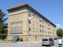 Grauer Wohnblock  in der Straße Čechova von  Budweis / České Budějovice - an der Hausfassade befindet sich ein Wandbild/Fresko mit einer Szene aus der Fischerei / Fischfang.