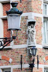 Madonna mit Kind, Steinskulptur an einer Hausfassade - alte Laternen; Bilder aus der historischen Innenstadt von Brügge.