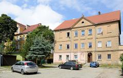 Schlichte mehrstöckige Wohnhäuser mit Mittelrisalit und Dreiecksgiebel - Parkplätze vor dem Haus, Bilder aus der Stadt  Peterswaldau / Pieszyce in Polen.