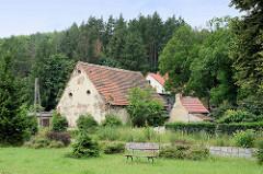 Gehöft, landwirtschaftliche Gebäude am Bach Kamionka  in  Pieszyce / Peterswaldau;  dahinter Wälder des Eulengebirges.