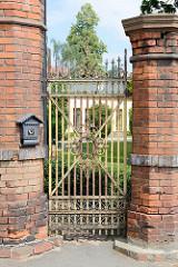 Hohe Ziegelmauer, eiserne Gittertür mit Schmuckelementen im Areal vom Schloss  Peterswaldau / Pieszyce.