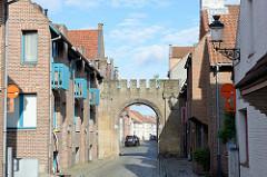 Neubauten mit türkisfarbenen Balkons und Fenstern in der Balsemboomstraat von Brügge; historisches Mauerwerk -  Tor zur ehemaligen Rademakers Kaserne, die in den 1970er Jahren abgerissen wurde.