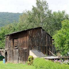 Große Holzhütte / Speicher aus rohen Holzbrettern im Eulengebirge von Pieszyce / Peterswaldau.