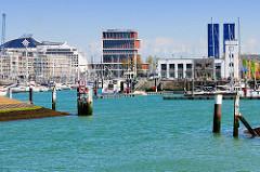 Hafenanlage / Sportboothafen in Seebrügge; links liegt ein Kreuzfahrtschiff hinter einem Gebäude mit Ferienwohnungen, rechts die alten Fischauktionhallen.