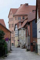 Historischen Bebauung in der Straße Bischofsberg der Hansestadt Havelberg - im Hintergrund ein mehrstöckiges Wohngebäude im Baustil des Historismus.