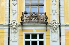 Historische Architektur im Kurort  Franzensbad / Františkovy Lázně; Hausfassade mit dekorierten Löwenköpfen und Balkongitter in aufwändigem Schmuck.