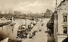 Altes Bild vom Fischereihafen in der Hansestadt Wismar; Boote liegen an den Kaimauern - am Ufer transportieren Pferdegespanne ihre Lasten.