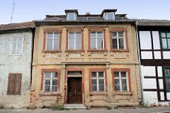 Denkmalgeschützte Wohnhaus in Havelberg - leerstehendes Gebäude mit Holztür und restaurierungsbedürftiger Fassade.