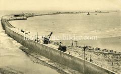 Altes Bild vom Bau der Hafenmole in Zeebrugge; ein Kran sowie eine Lokomotive stehen auf den verlegten Bahngleisen.