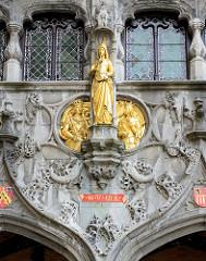 Vergoldete Figuren an der Fassade der Heilig Blut Basilika in Brügge - der Sakralbau ist Relikien-Aufbewahrungsort einer Ampulle mit dem Blut Christi. Die jährlich an Christi Himmelfahrt stattfindende Heilig-Blut-Prozession ist von der UNESCO in d