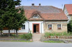 Doppelhaus mit unterschiedlicher Fassadengestaltung und bepflanzten Vorgärten, halbrundes Dachfenster / Dachgaube mit Ziegeln gedeckt, Wohnhaus in Pieszyce / Peterswaldau.