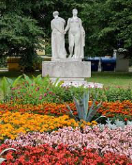 Steinskulptur, Frauengruppe in einer Grünanlage von  Franzensbad / Františkovy Lázně.