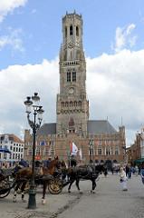Grote Markt von Brügge, Touristen können mit  Pferdedroschken eine Stadtrundfahrt unternehmen - Blick auf den Brügger Belfried.