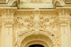 Eingangsportal eines neoklassizistischen Gebäude  in der Kuranlage von  Franzensbad / Františkovy Lázně;   spärlich bekleidete halbnackte Frauen und Blumen gelangten zieren die Fassade des Gebäudes.