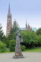 Bronzestatue von Papst Johannes Paulus II in Bielawa/Langenbielau dahinter der hohe Kirchturm der  Kirche Maria Himmelfahrt; geweiht 1876 - Architekt Alexis Langer.