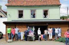 Bekleidungsgeschäft in Peterswaldau / Pieszyce - Schaufensterfiguren mit Hosen und T-Shirts stehen auf dem Fußweg, Kundinnen sehen sich die Sachen an.