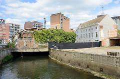 Mit Efeu bewachsenes verfallenes Lagergebäude im Hafengebiet von Löwen/Leuven der Fluss Dijle fließt  dort durch einen Tunnel.