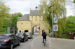 Straßenverkehr, wartende Autos vor dem Smedenpoort / Schmiedtor in der Stadt Brügge. Das Tor war Teil der Befestigungsanlage, die 1368 wieder angelegt wurde.