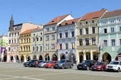 Historische Randbebauung am Marktplatz in der Innenstadt von Budweis; Wohn und Geschäftshäuser mit farbiger Fassade und Colonnaden; parkende Autos.