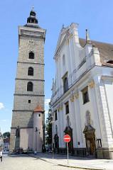 Rechts die Fassade der Kathedrale St. Nikolaus – Katedrála svatého Mikuláše in Budweis / České Budějovice . Das barocke Kirchengebäude wurde 1640 beendet, die Baumeister waren Baumeister J. Cipriani und F. Canevalle. Links der Schwarze Turm / Černá