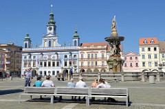 Blick über den Marktplatz zum historischen Rathaus von Budweis /  České Budějovice. Das Bauwerk im Stil des Barock wurde 1730 nach den Plänen des Architekten Anton Erhard Martinelli errichtet. Rechts der Samsonbrunnen / Samsonova kašna - früher Teil
