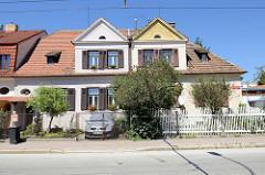 Doppelhaus in der tschechischen Stadt   Budweis /  České Budějovice; das Gebäude ist teilweise renoviert, das Dach der   einen Hälfte wurde neu eingedeckt und die Fassade gestrichen - die Gartenfront wird mit unterschiedlichen Gartenzäunen zur Straß