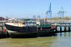 Alter Fischereihafen  in Seebrügge, ein Fischerboot liegt am Steg, dahinter Hafenkräne.