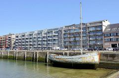 Hafenfront des alten Fischereihafens in Seebrügge, ein Holzboot liegt am Kai - mehrstöckige Gebäude mit Ferienwohnungen stehen an der Hafenpromenade.