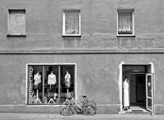 Bekleidungsgeschäft in Peterswaldau / Pieszyce - schlichte Hausfassade mit Rauhputz, Schaufensterfiguren ohne Kopf tragen Kleider/Pullover; ein Fahrrad ist eine Fassade angelehnt.