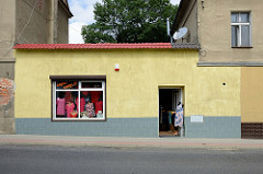 Bekleidungsgeschäft in Peterswaldau / Pieszyce - Schaufensterfiguren mit Blusen und Kleidern stehen im Schaufenster und im Eingang.