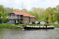 Vereinsgebäude des Koninklijke Roeivereniging Brugge, dem 1869 gegründeten Ruderclub der Stadt - eine Barkasse fährt auf dem Gent-Oostende-Kanal.
