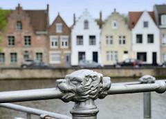 Historisches Geländer am Langen Kai in Brügge; im Hintergrund Wohnhäuser mit Treppengiebel an der Potterierei.